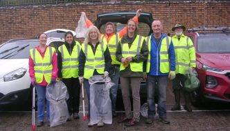 a group of people in hi-viz vests standing in front of a wall ready to litter pick in Newton Abbot