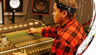 a woman in a red and balck checked shirt at a mixing desk