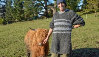 a man in a long grey jumper and woolly hat is stood next to a shorter brown cow with horns