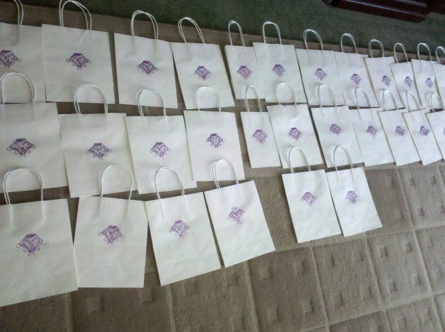 Logo gift bags drying after stamping and adding glitter paint