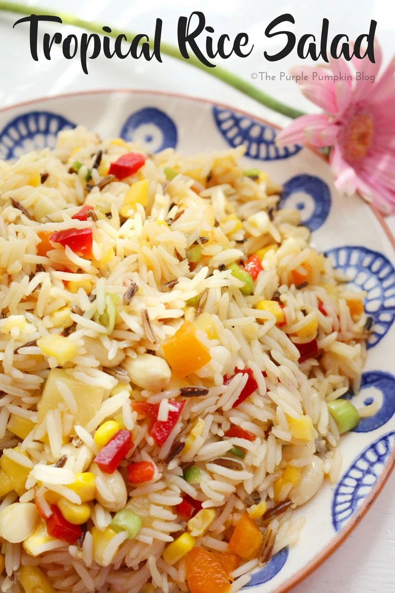 A rice salad filled with finely chopped peppers, onion, pineapple, mango, chilli, and sweetcorn, sitting on a blue print plate.