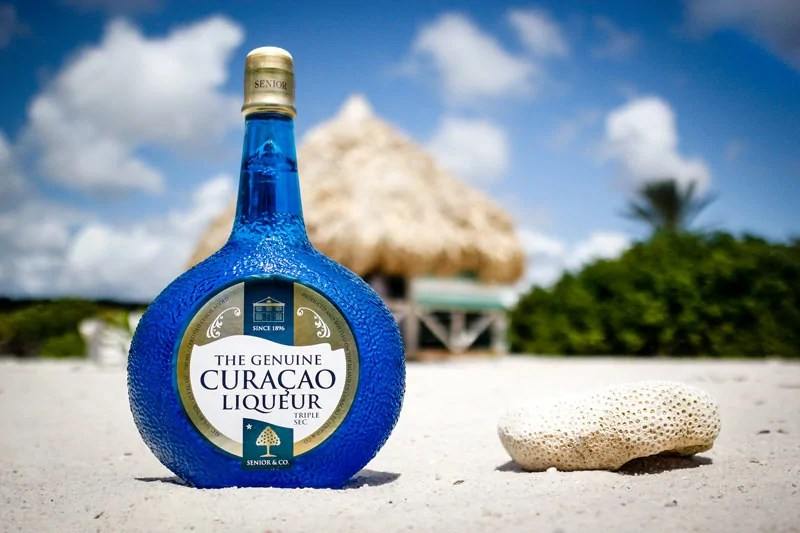 Bottle of Blue Curaçao on a beach