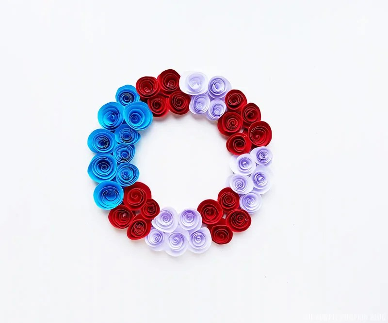 Completed homemade paper flower wreath with red, white, and blue paper roses on a white background.