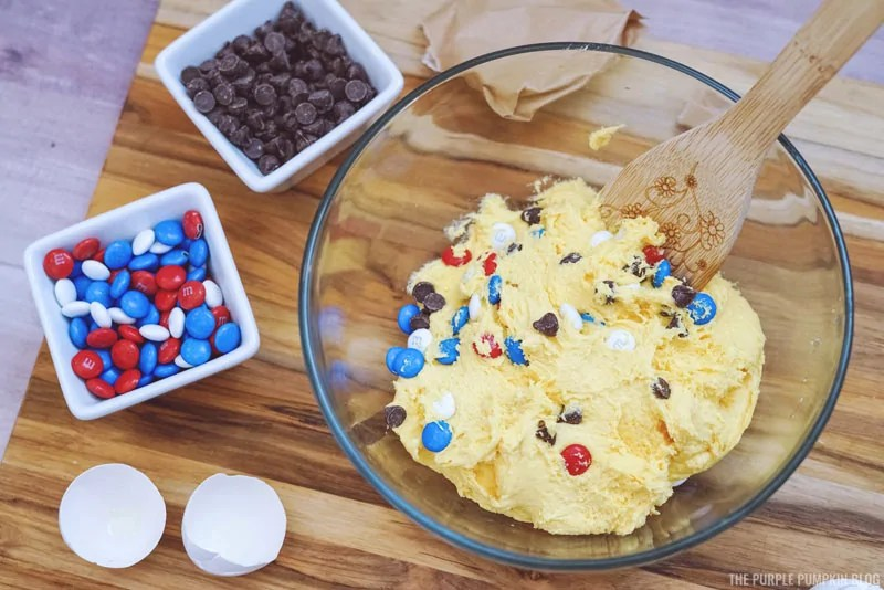 Cookie dough in a bowl with chocolate chips and m&m's