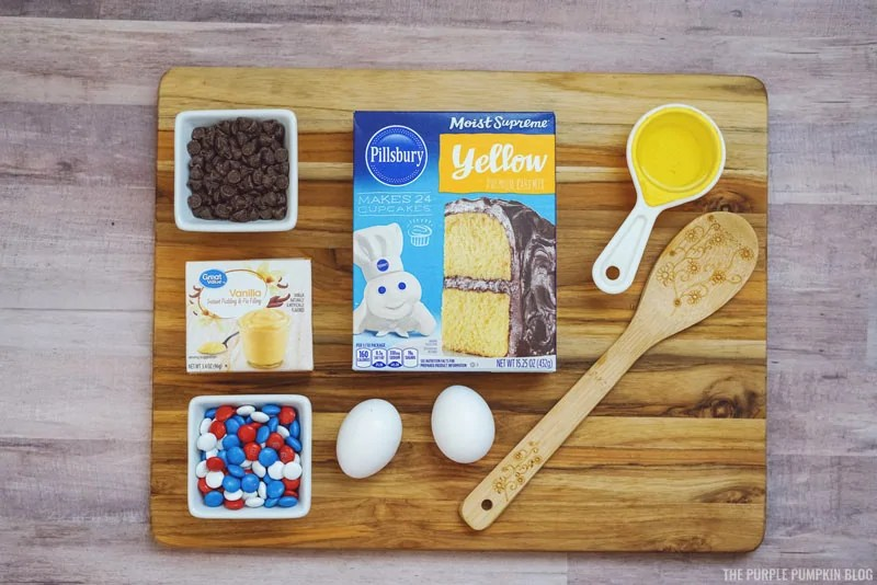 A wooden board with cookie bars ingredients, including a box of yellow cake mix, a box of vanilla pudding mix, chocolate chips, candy, eggs, and cooking utensils.