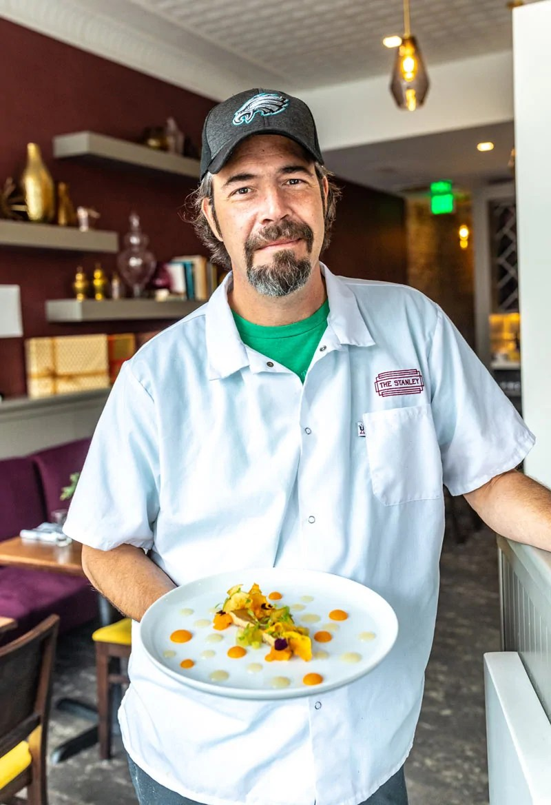 Headshot of The Stanley's, owner and chef, Paul Verica Holding Entree Dish
