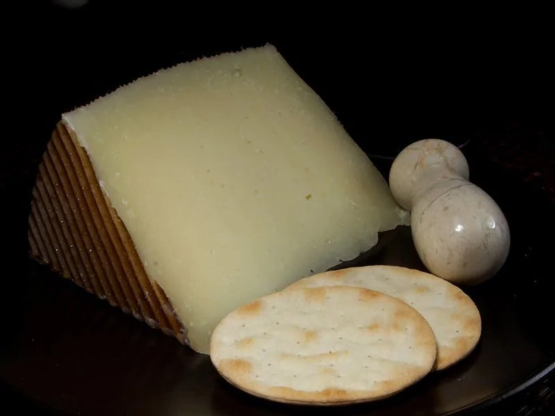 A wedge of Manchego cheese, with a cheese knife and a couple of cheese crackers.