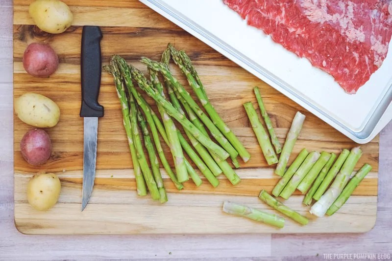 Asparagus and mini potatoes on a chopping board, with a knife and sheet pan to one side.