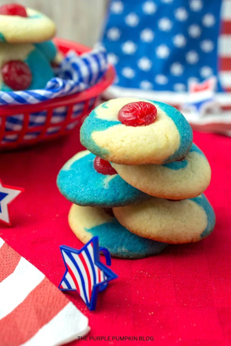 Stack of red, white, and blue cookies with a cherry on top, placed on a red napkin, with star shaped trinkets around it.