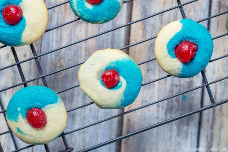 red, white, and blue cherry almond thumbprint cookies on a wire cooling rack