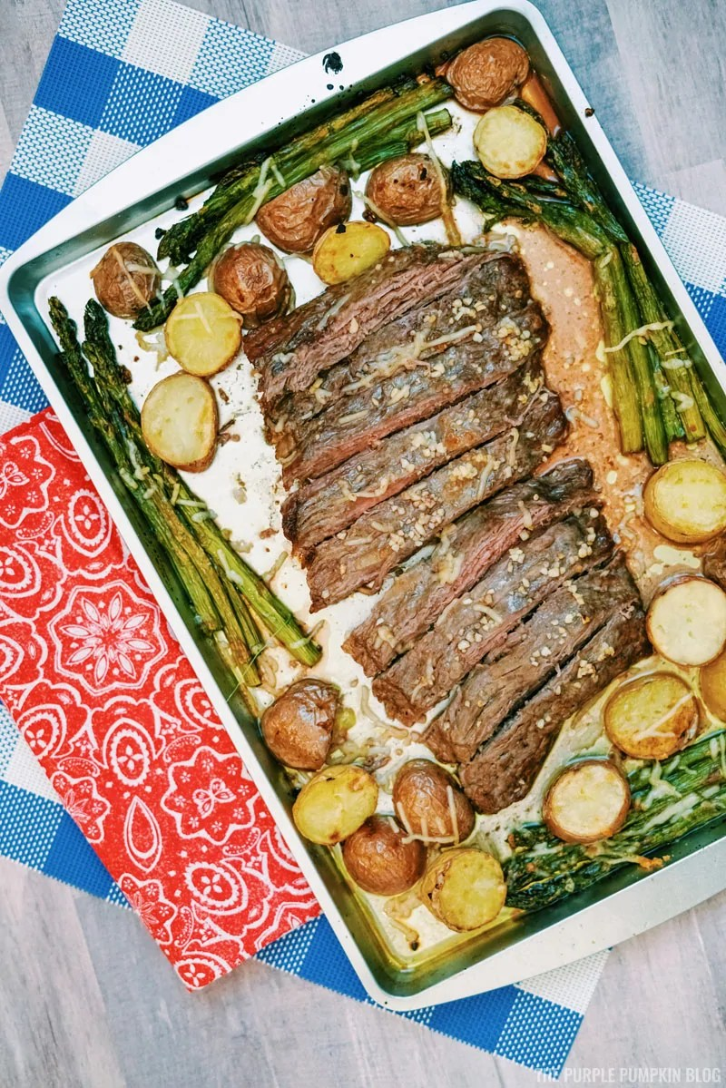Sheet pan steak dinner - cooked steak with asparagus and mini potatoes on a silver sheet pan, placed upon a table with blue and red napkins