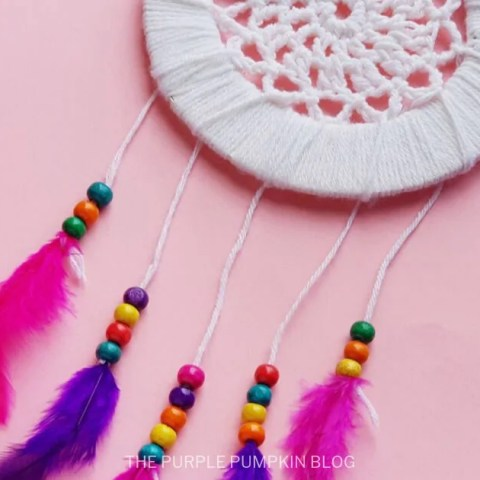 A DIY Dremcatcher with purple and pink feathers