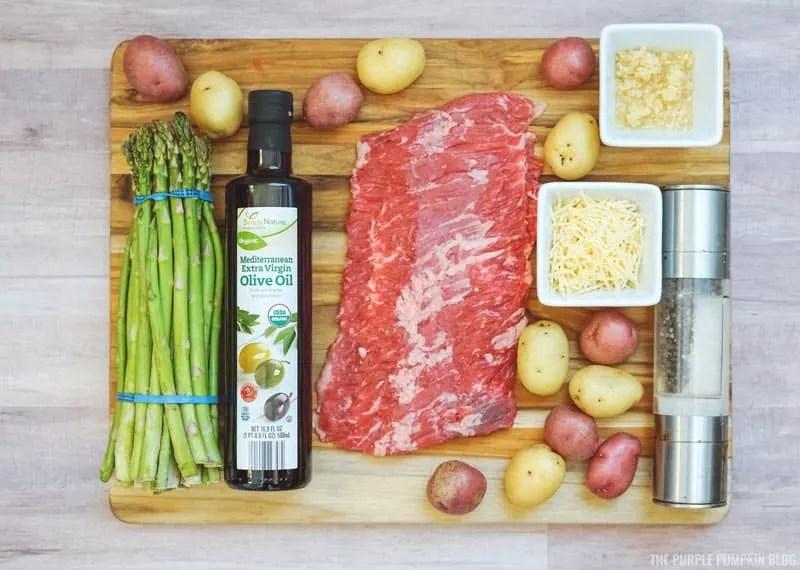 Ingredients for Sheet Pan Steak Dinner: Asparagus, mini potatoes, garlic, olive oil, parmesan, skirt steak, and salt and pepper