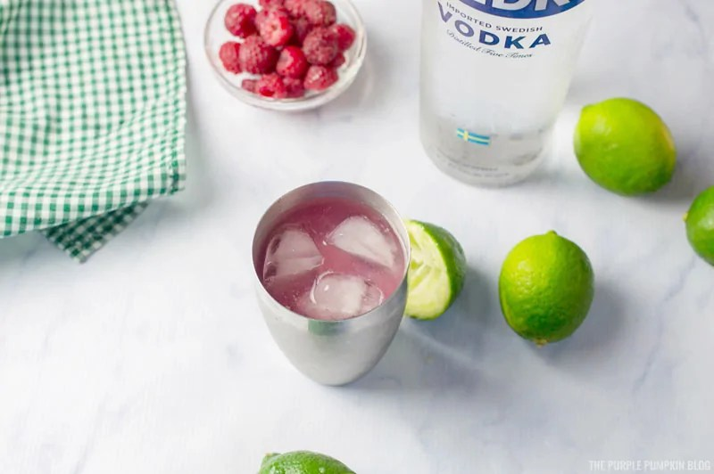 Raspberry lime vodka cocktail in cocktail shaker with ice. Surrounded by limes, vodka bottle, and bowl of raspberries