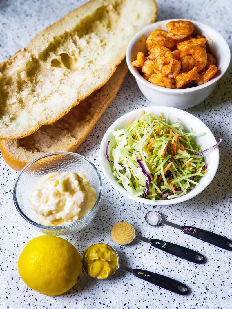 Shrimp Slaw Sandwich ingredients - but loaf of bread, cooked shrimp, slaw mix, mayo, dijon, garlic powder, lemon, sald.