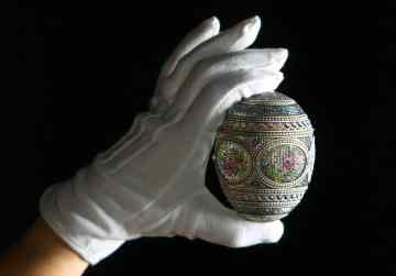 A curator from the Royal Collection examines a mosaic egg, made by Russian jeweller and goldsmith Peter Carl Faberge which was originally commissioned by Tsar Nicholas II in 1914 and acquired by Queen Mary in 1933, part of the new Faberge exhibition at Buckingham Palace, London, opening on Saturday 23 July. (Photo by Dominic Lipinski/PA Images via Getty Images)