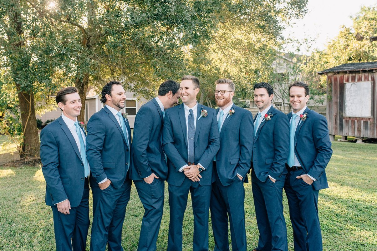 grooms men laughing with groom