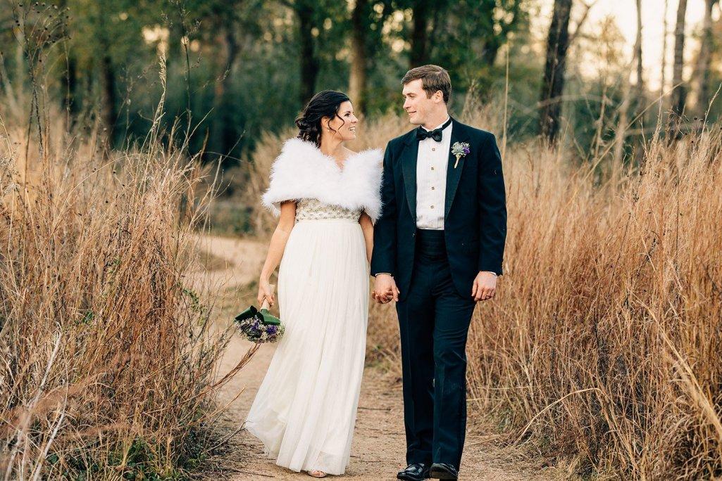 bride and groom walking on trail at Houston arboretum