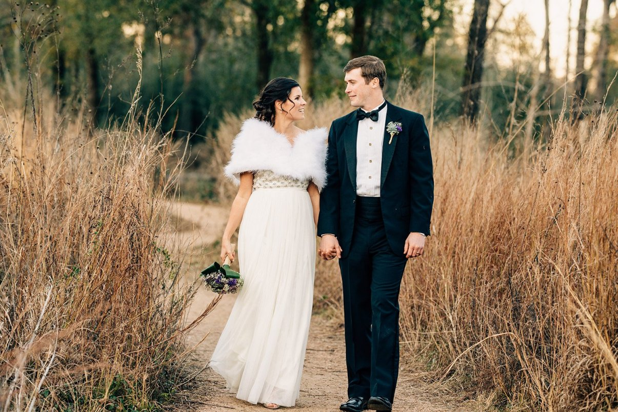 bride and groom walking on trail at Houston arboretum