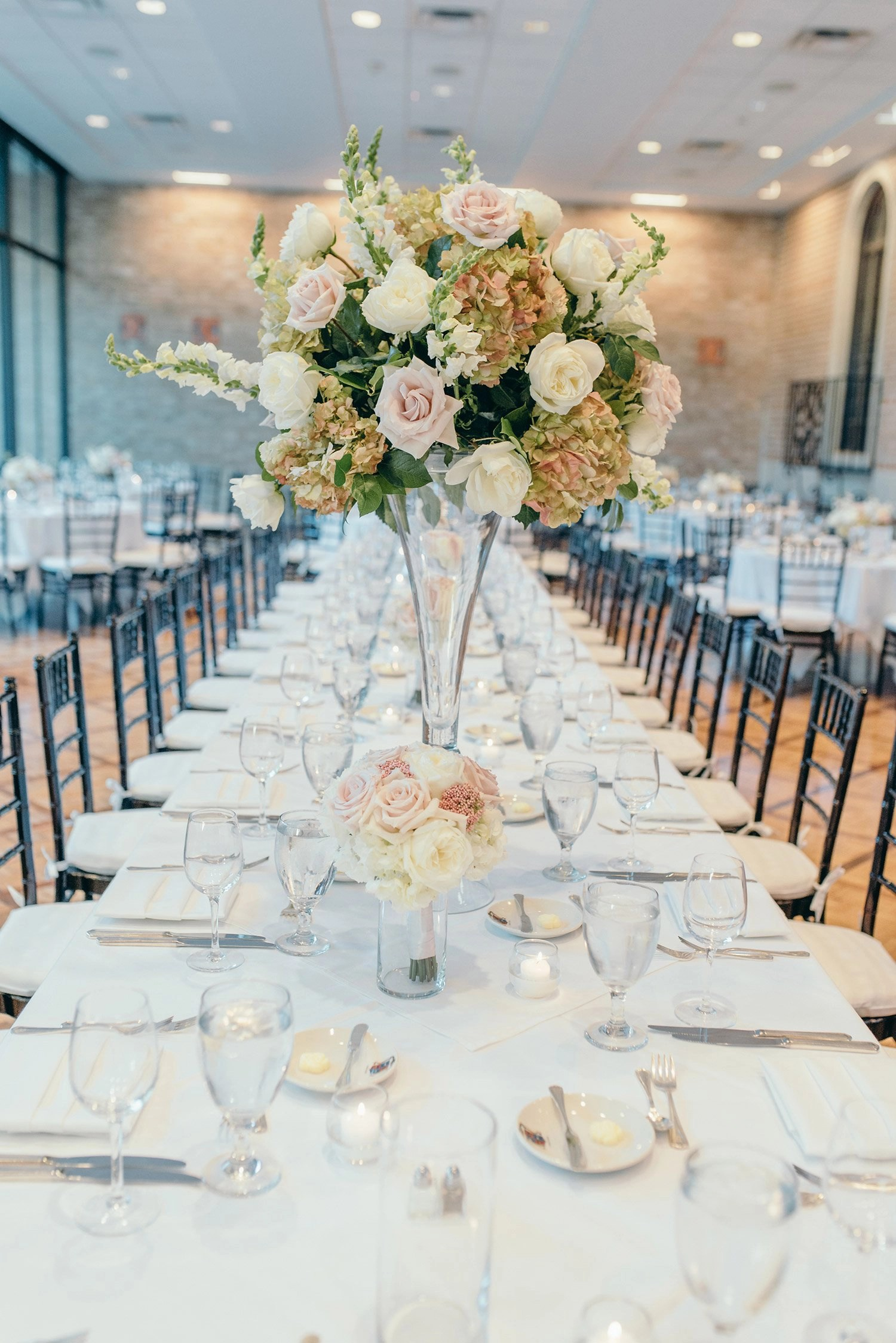 floral centerpiece on long tables with white table lines and black chiavari tables in Rice Unviversity's Cohen House Wedding Reception