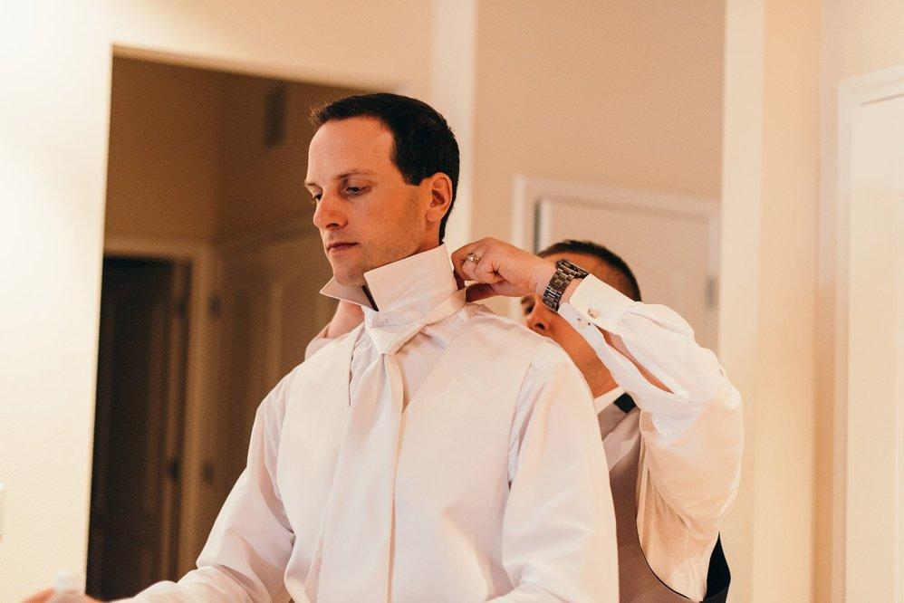 groomsmen helping groom get ready