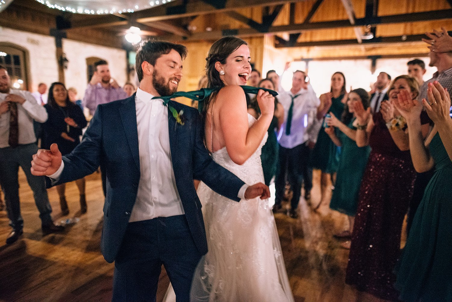 bride leads groom around the dance floor by his tie