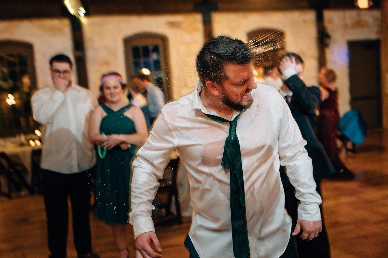 groomsmen covered in water on dance floor
