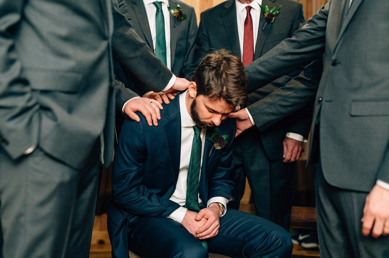 groomsmen pray for groom before his wedding