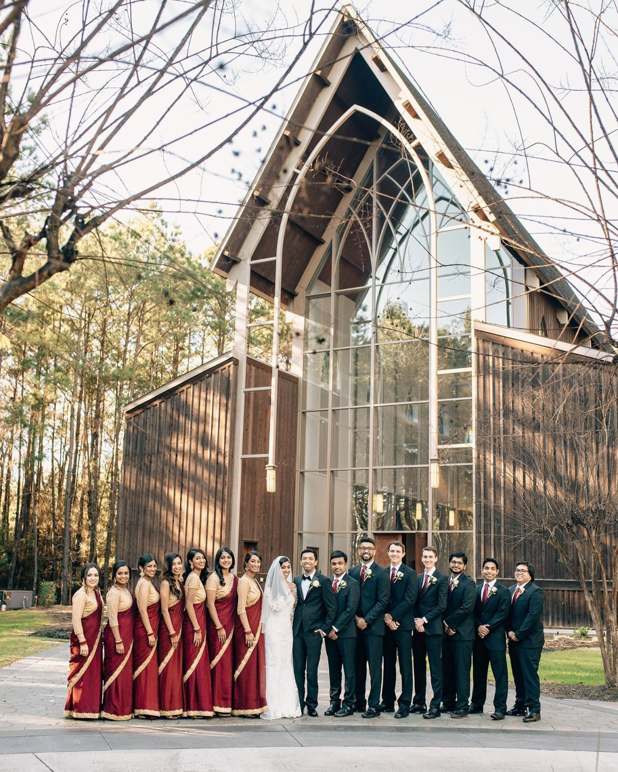 wedding party in front of the chapel in the woods