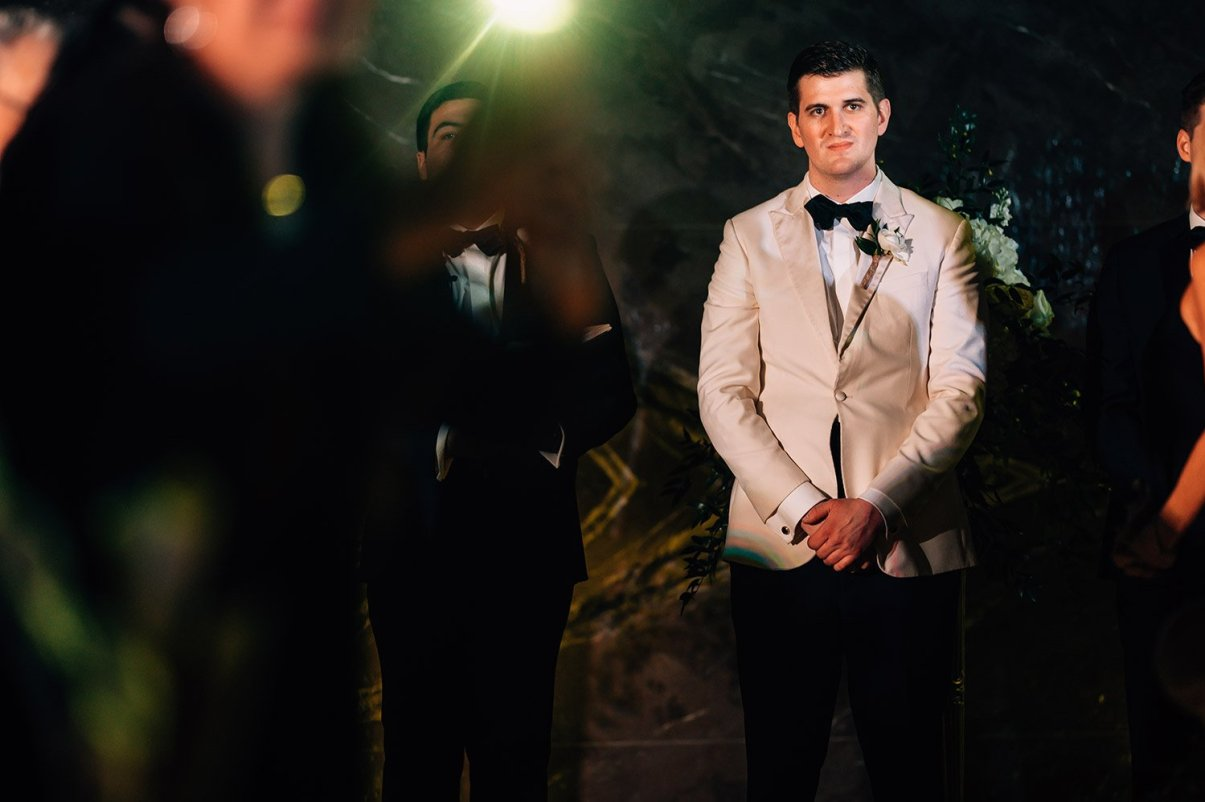 groom seeing bride come down the aisle at night at the Hotel Galvez