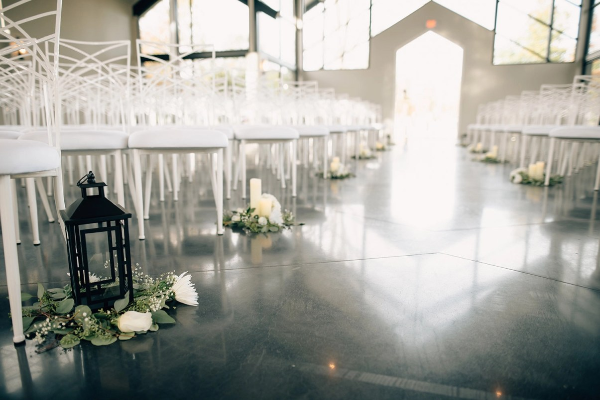 lanterns and roses in aisle of jennings trace wedding