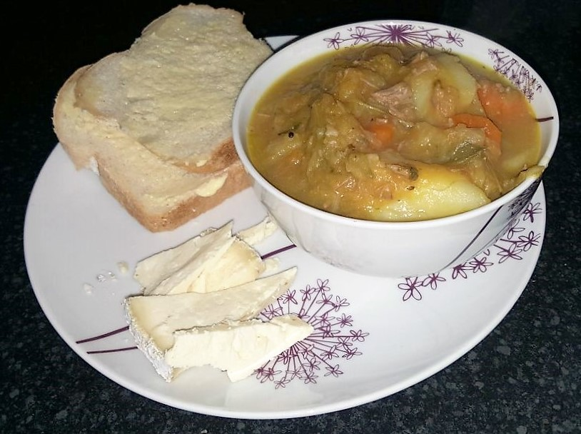 A bowl of stew with bread, butter and cheese