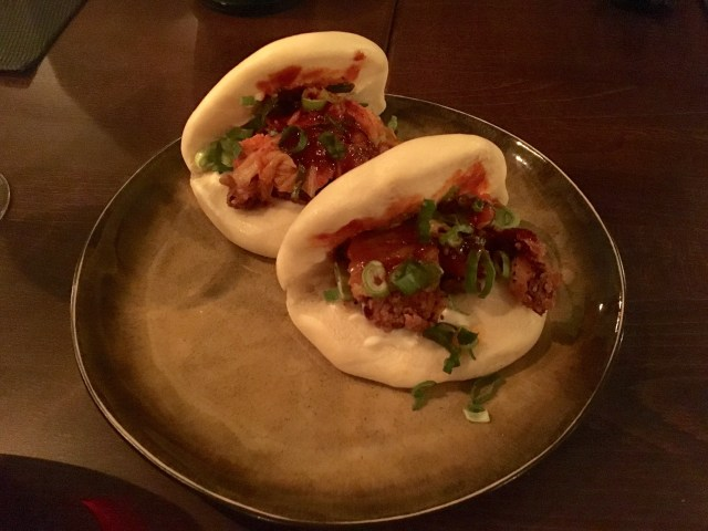 Two bao dumplings filled with fried chicken and spices