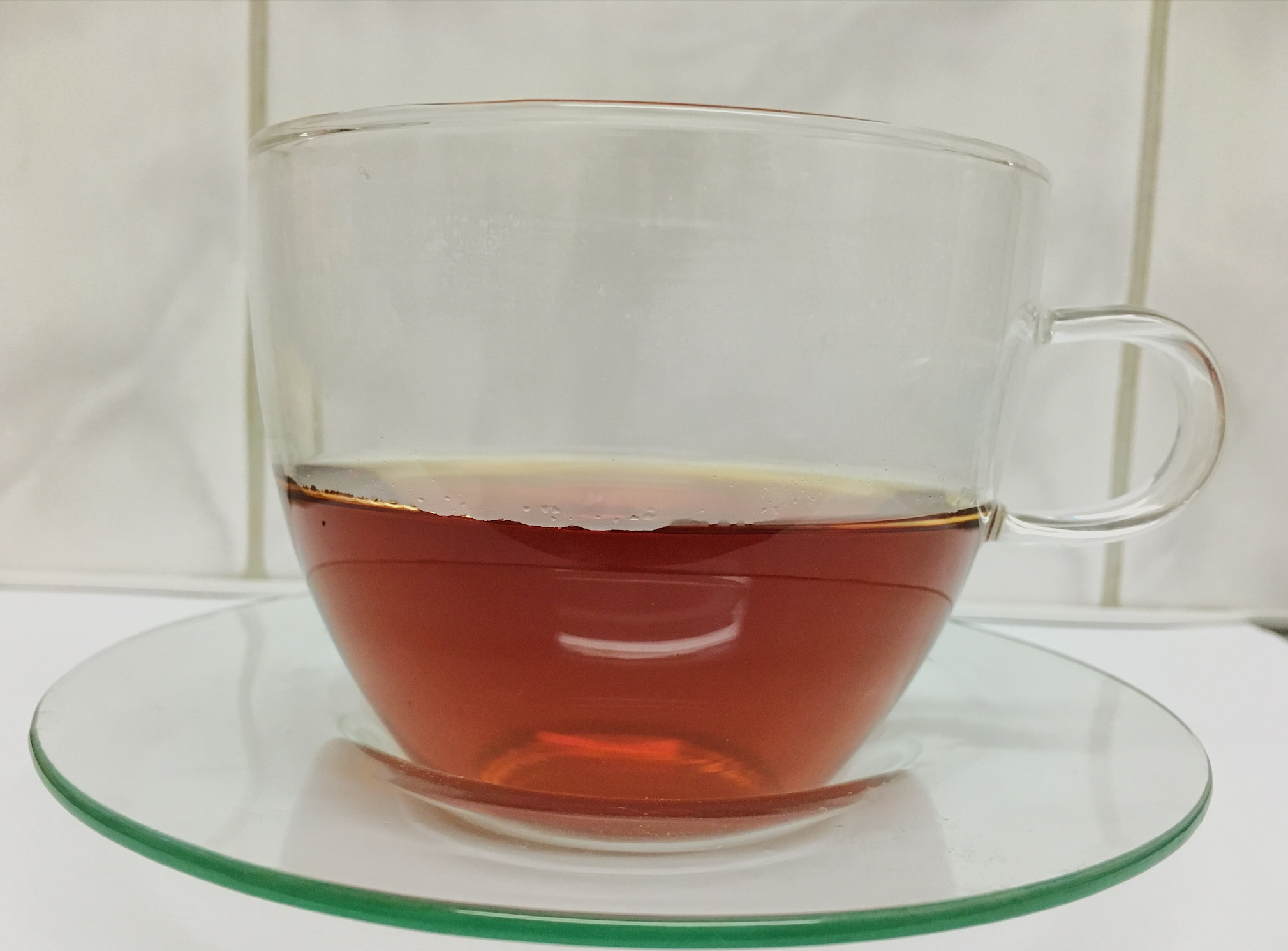 Brewed tea in a glass cup and saucer