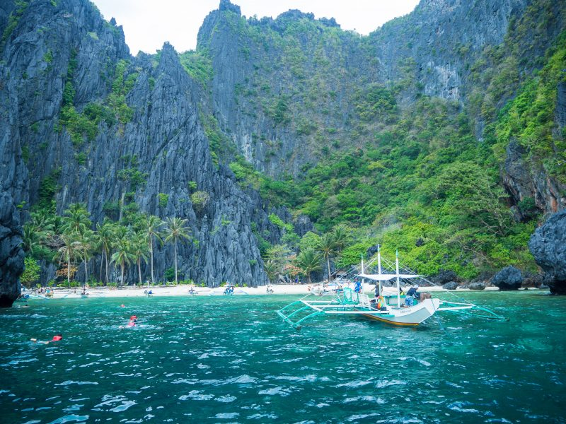 A boat on turqoise waters at a white sand beach in the Phillipines
