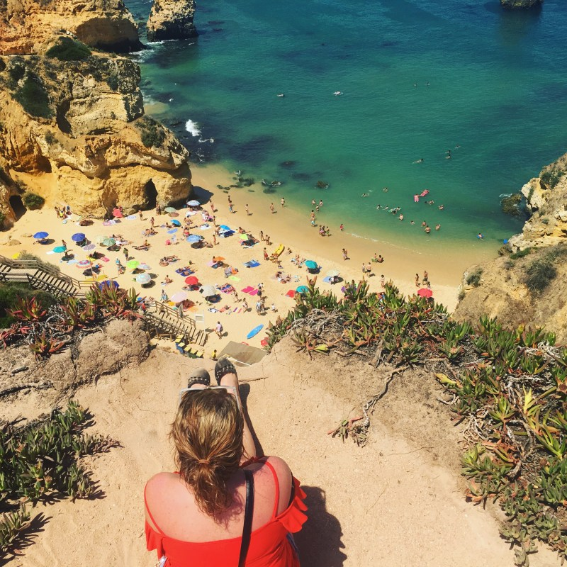 Me sitting on a sandy cliff overlooking a beach in Lagos, Algarve - a great destination for an amazing travel experience