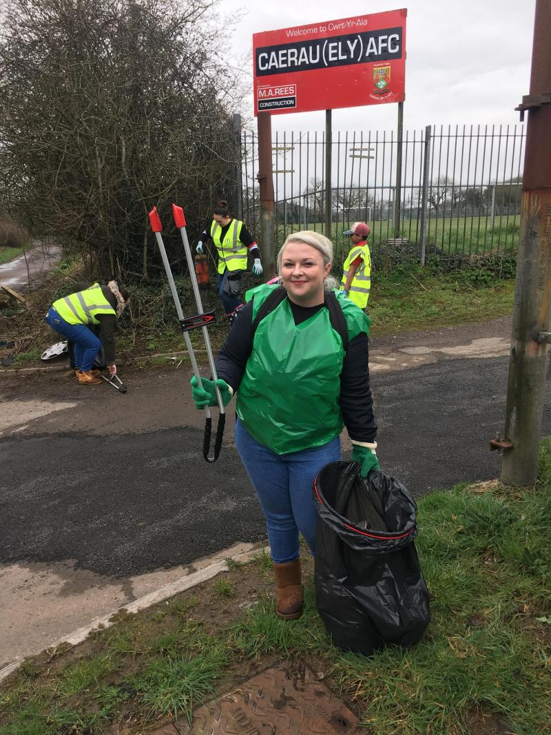 Me wearing a green plastic vest, holding a litter picker and black bin bag underneath the 'Caerau Ely F.C' sign