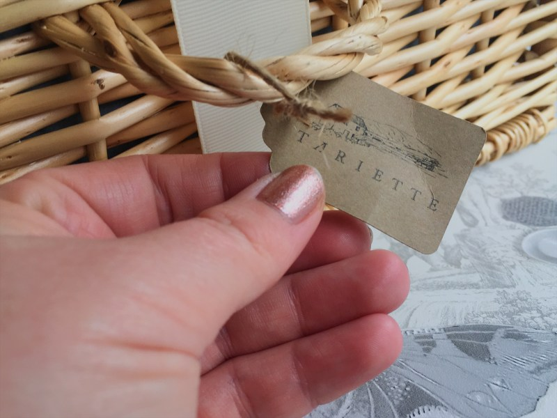 A hand holding the Tariette-branded brown card label on Tariette's Provencal food hamper