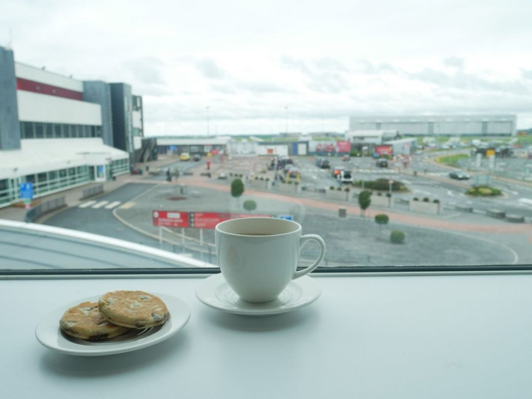 A plate of freshly baked Welsh cakes and a cup of Welsh brew tea in Cardiff Airport's Executive Lounge, overlooking the car park and airport entrance.