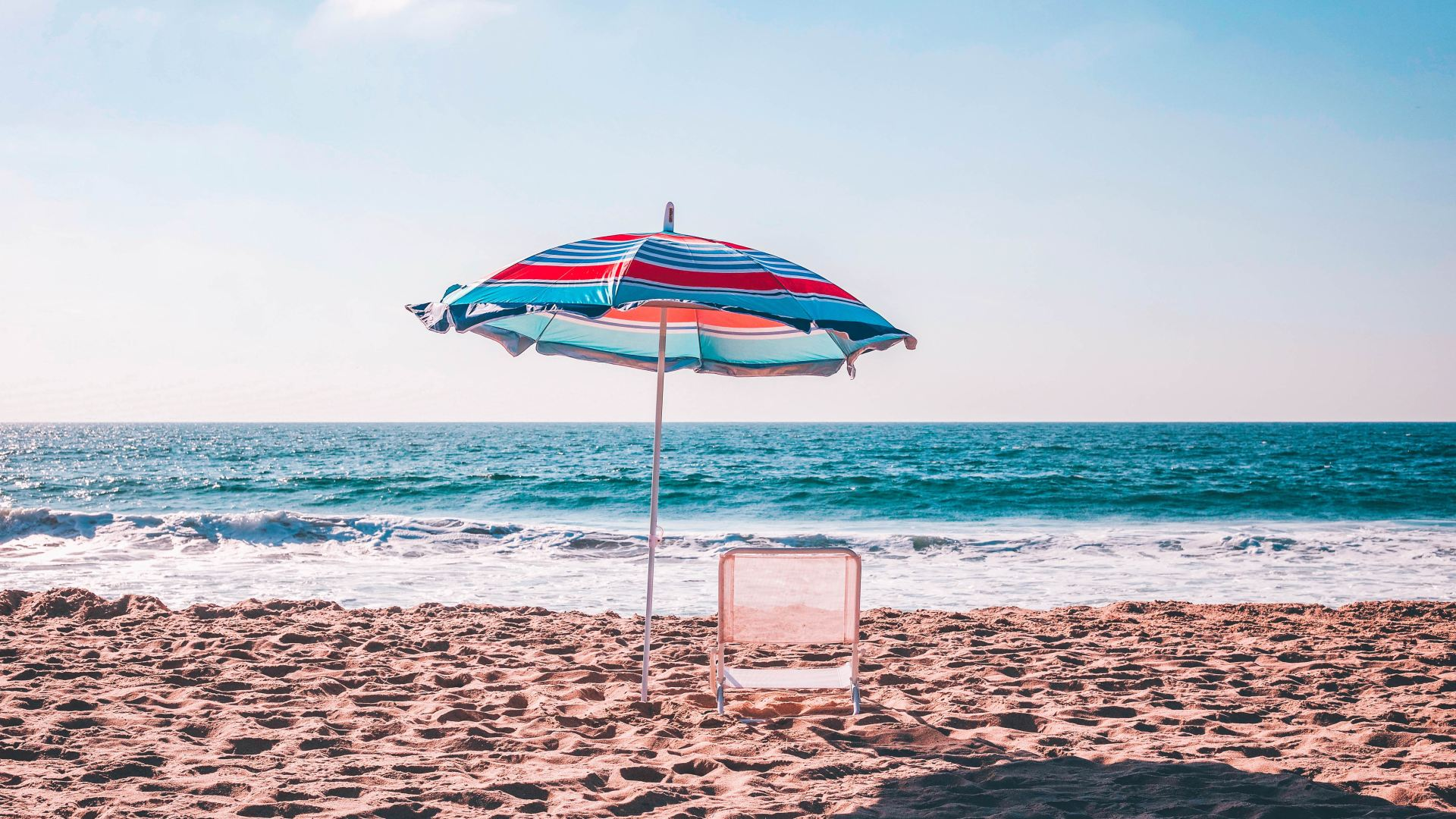 beach with an umbrella and deck chair facing the sea