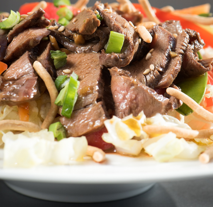 This hearty Asian Steak Salad is loaded with healthy vegetables, tender grilled steak and topped with a dressing that'll knock your socks off! | The Recipe Wench