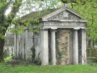 A mausoleum covered in ivy stands alone in a cemetary