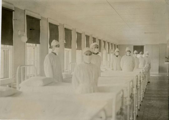 Attendants, fully covered, wait along rows of empty beds in a hospital ward