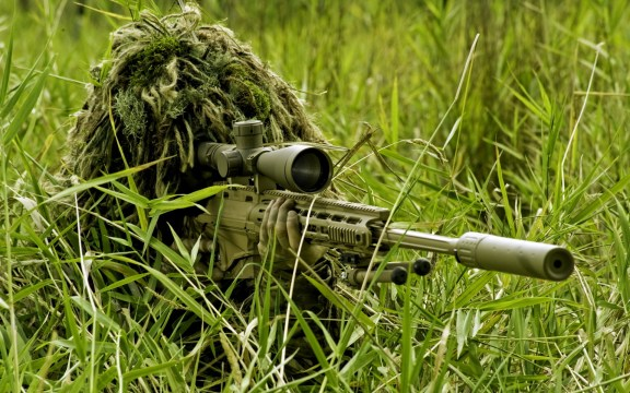 A sniper is in the grass wearing a ghillie suit.