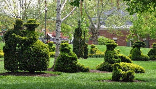 Topiary shaped like people sitting in a park