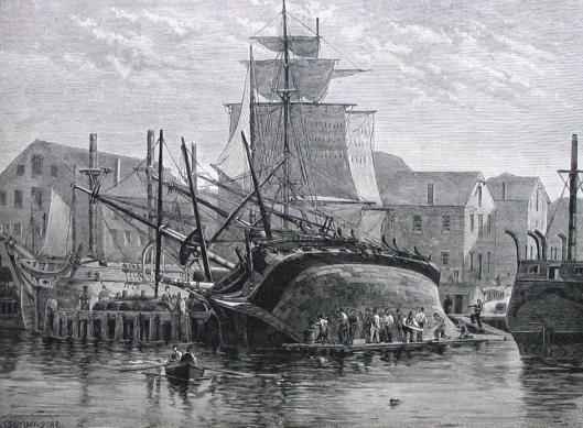 An old ship  on it's side being careened while in  dry dock