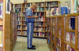 Inmate in library seeking spiritual growth books