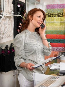 Young woman, owner of gift shop, talking on mobile phone behind checkout counter, holding clipboard
