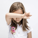 young girl with arm covering her eyes