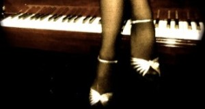 Female legs draped over a piano keyboard